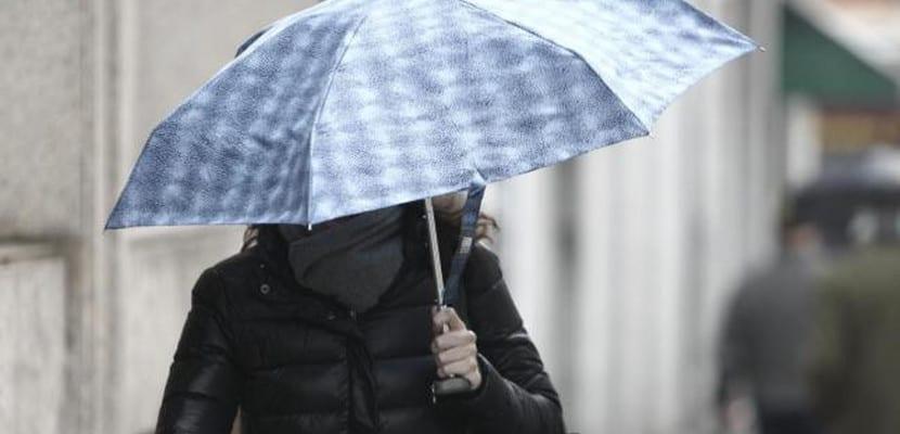 Mujer camina bajo un paraguas en un día lluvioso