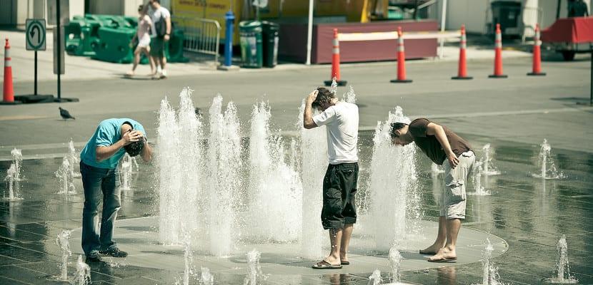 Personas se refrescan en una fuente durante una ola de calor