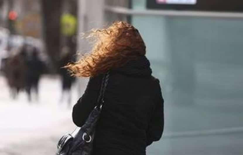 Mujer camina con fuerte viento