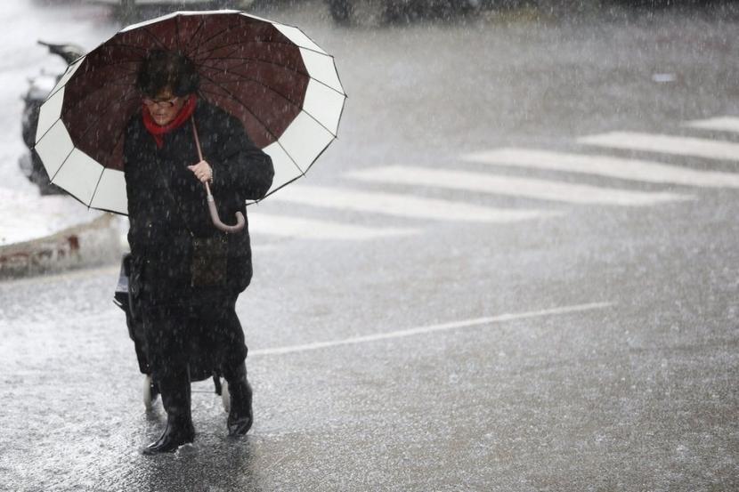 Mujer se protege de la lluvia