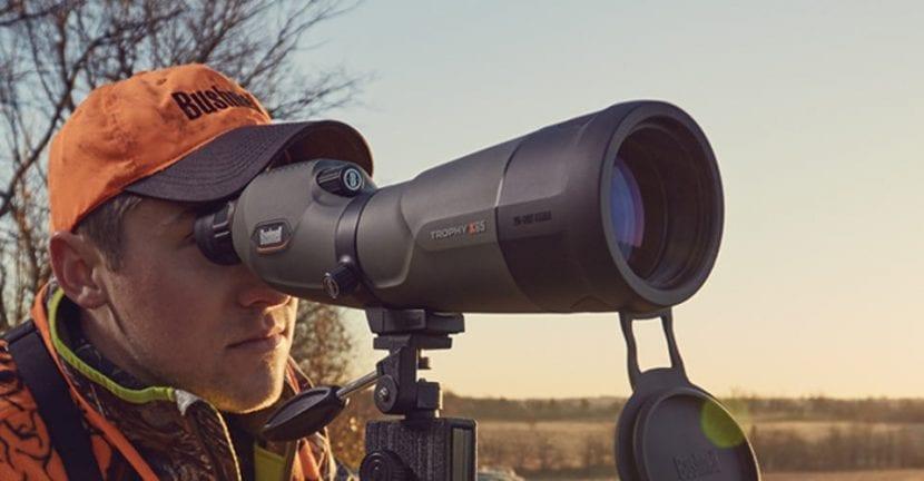 Hombre mirando por un telescopio terrestre
